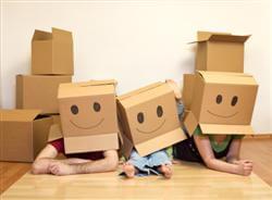 זוג עם ילדים משתעשע עם קרטונים לצורך הובלה