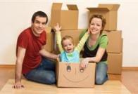 משפחה בביתה החדש יושבת על הרצפה עם קופסאות קרטון מסביב