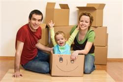 Happy family in their new home sitting on the floor with cardboard boxes around
