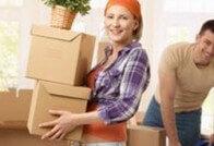 אשה נושאת קרטונים לאריזה של דירה