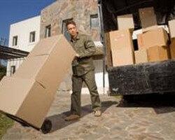 איש חברת הובלות מעביר קרטונים על עגלה